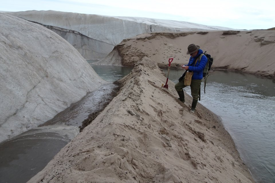 researcher collecting sand from meteorite